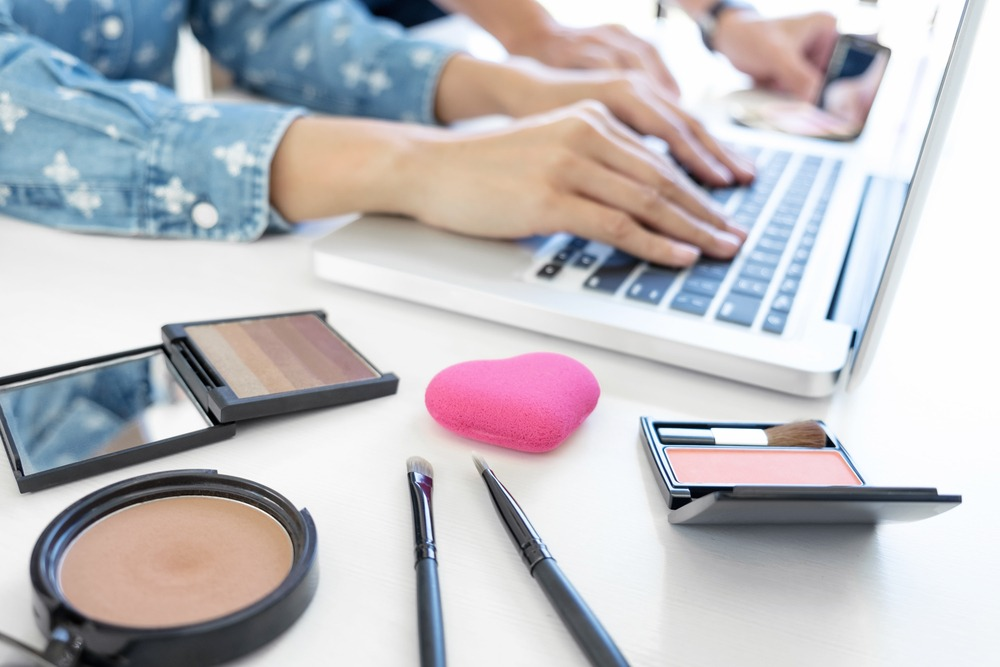 Illustration of cosmetics next to a laptop, we deliver information of buying cosmetics.