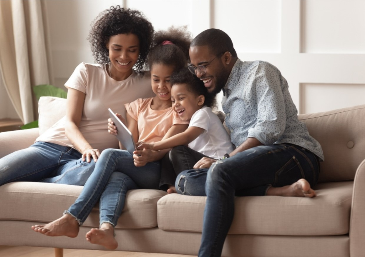 An image of a family smiling together on a tablet. Cyber Hero provide steps you can take as a parent when it comes to your child being cyber bullied.