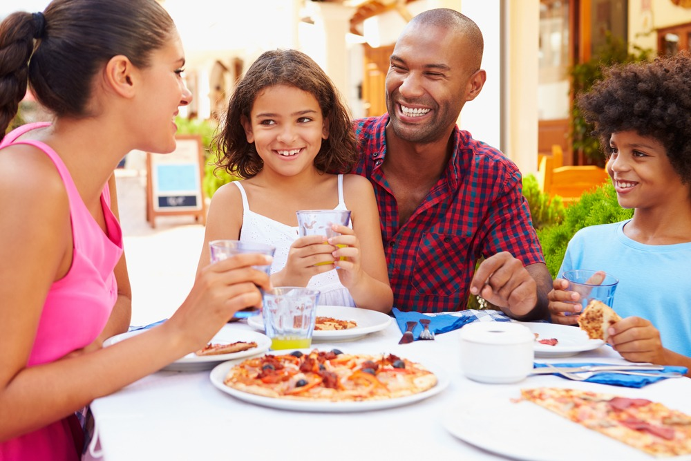 An image of a family out to eat, Cyber Hero provide information on digital detoxes and creating family agreements.